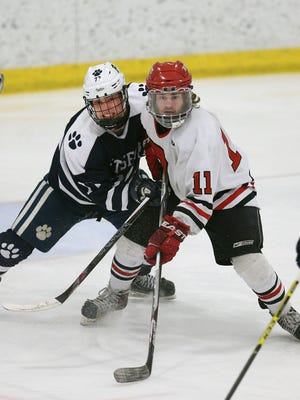 Pittsford's Brendan Haims (77) tries to clear Penfield's Adam Witscheber from in front of the net.