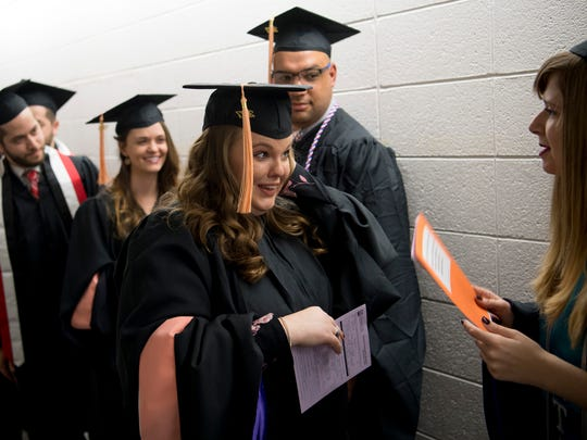 Rachael Sherwood, left, and Cassandra Peterson, both earning combined Bachelor of Science and Master of Science degrees, prepare to receive their diplomas at the University of Evansville's Winter Commencement in the Student Fitness Center Gym Thursday afternoon.