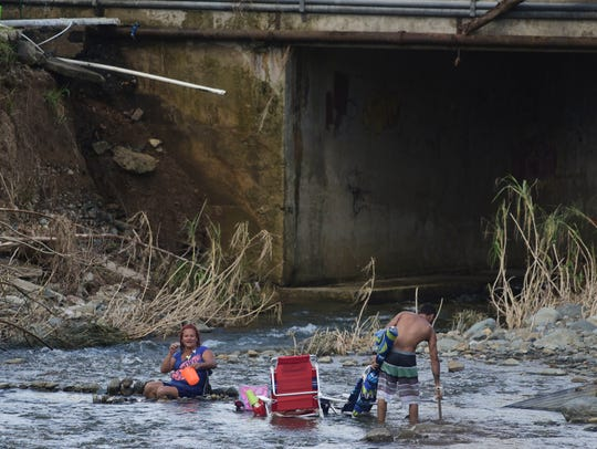 A couple bathes in the Gurabo River in the aftermath