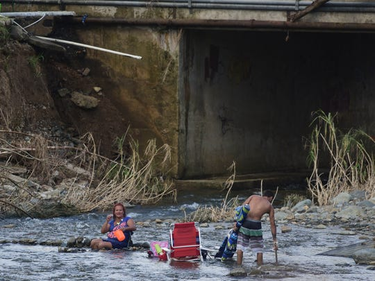 A couple bathes in the Gurabo River in the aftermath of Hurricane Maria in Las Piedras, Puerto Rico, Monday, Oct. 2, 2017. Power is still cut off on most of the island, schools and many businesses are closed and much of the countryside is struggling to find fresh water and food. (AP Photo/Carlos Giusti)
