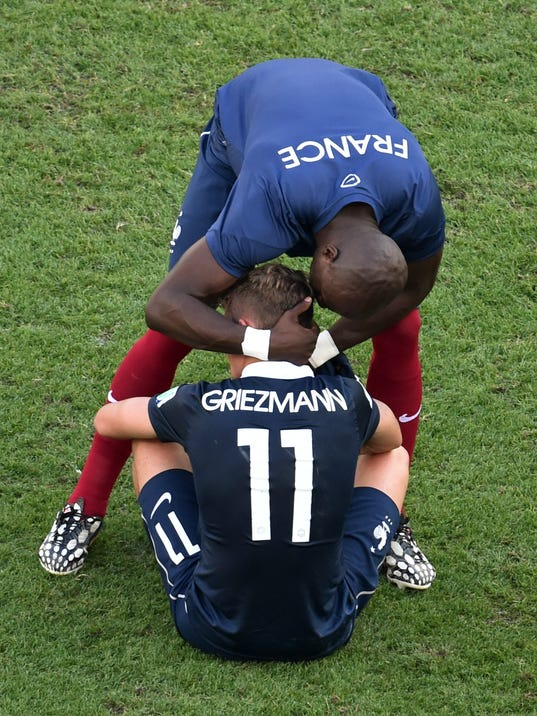 France's Antoine Griezmann is consoled by a team member after the World Cup quarterfinal soccer match between Germany and France at the Maracana Stadium in Rio de Janeiro, Brazil, Friday, July 4, 2014. Germany won 1-0. (AP Photo/Francois Xavier Marit, pool)