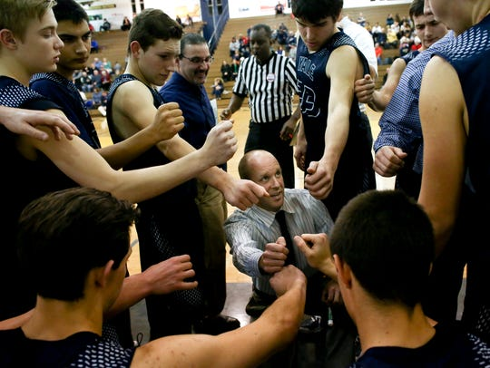 Yale players put their hands in a huddle with coach