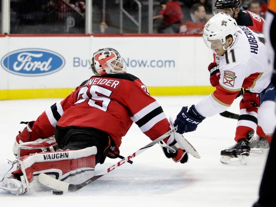 New Jersey Devils goalie Cory Schneider (35) blocks a shot by Florida Panthers left wing Jonathan Huberdeau (11) during the first period of an NHL hockey game, Saturday, Nov. 11, 2017, in Newark, N.J. (AP Photo/Julio Cortez)