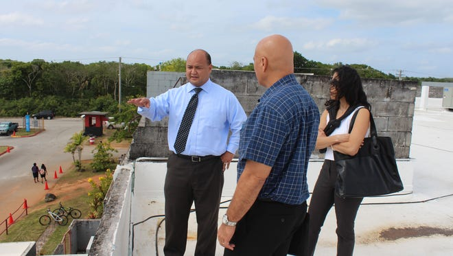 in this Feb. 16 file photo, Guam Department of Education Superintendent Jon Fernandez, left, shows Department of Public Works Director Glenn Leon Guerrero areas of concern on the roof of Simon Sanchez High School.