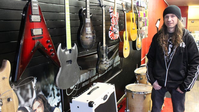 Jeff Sandbom, owner of Sandbom Guitar, stands next to guitars that he built at his new shop at 626 N. Third Ave., Wausau.