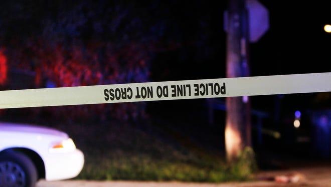 Crime scene tape cordons off the scene of a homicide.