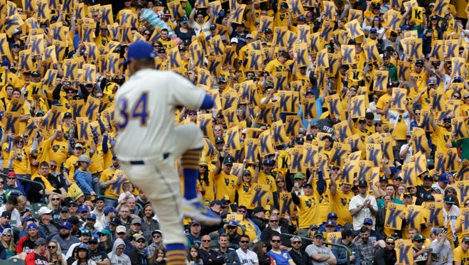 """Seattle Mariners starter Felix Hernandez winds up to pitch against the Oakland Athletics during the fourth inning of a baseball game Sunday, April 10, 2016, in Seattle. Fans, background, hold signs with the letter """"K"""" for a strike, in the """"King's Court"""" based on a nickname for Hernandez: """"King Felix."""""""