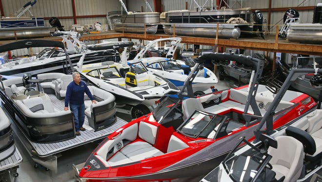 Tim Tinus looks over some of his inventory at Tinus Marine in Oconomowoc. In late January, Tinus Marine will host its first in-person boat show.