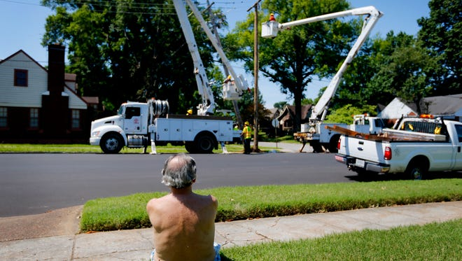 May 30, 2017 - Gene Paccasassi, kills time by watching crews with Davis H. Elliot Co. from Lexington, Ky. work to repair damaged utility poles in his neighborhood on Vollintine caused by downed trees. Memphis continue to recover from the Saturday storm that caused the third worst power outage in MLGW history.