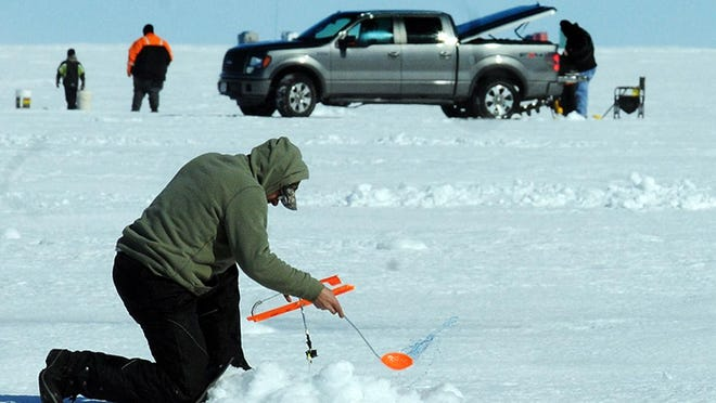Jerry LeMere of Brussels uses a slush dipper to clear slush from a fishing hole off Little Sturgeon in 2014.