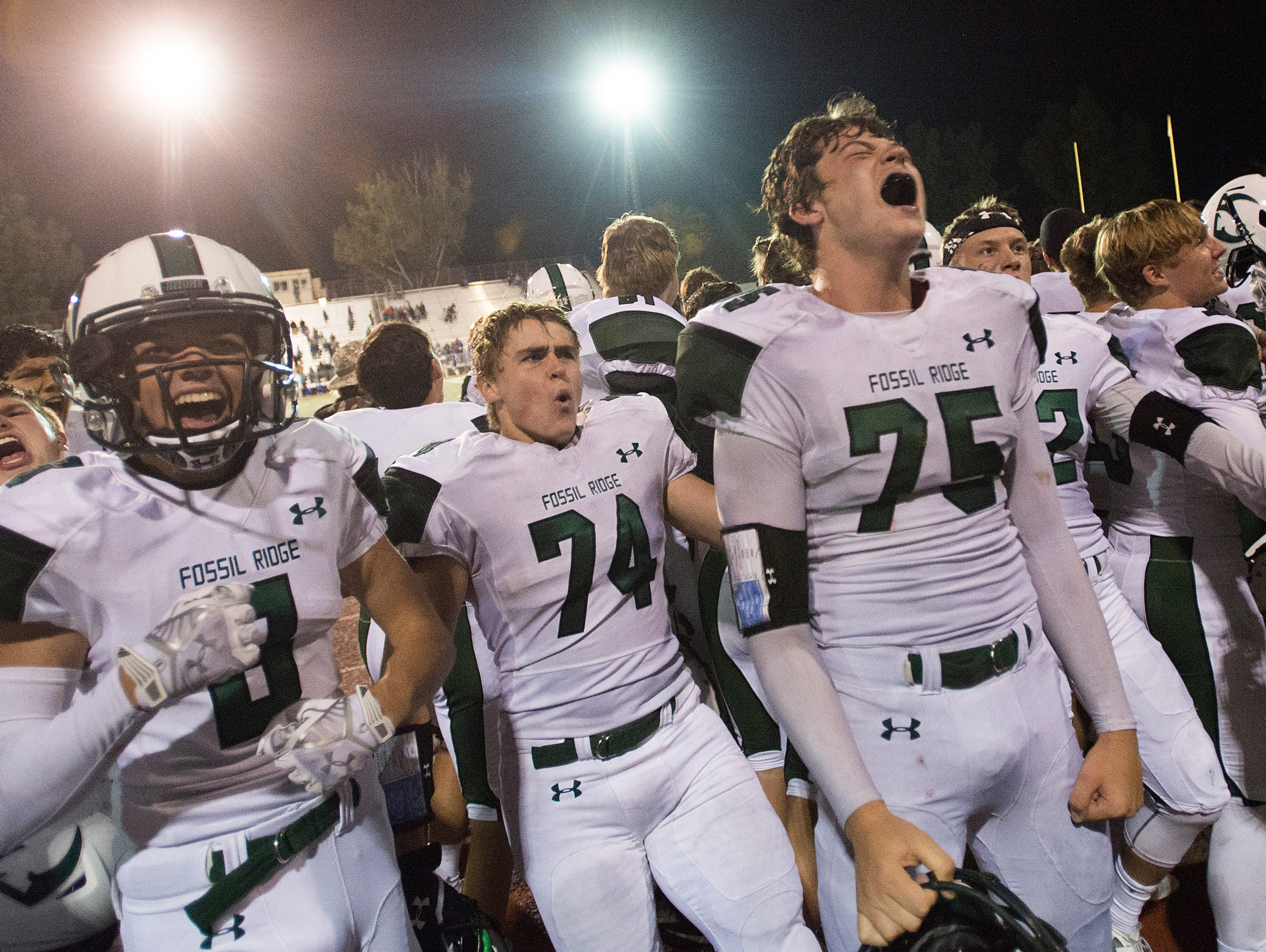 Fossil Ridge High School football players celebrate a 17-14 win over Poudre at French Field Friday, October 2, 2015. A field goal in the final seconds of the game allowed the SaberCats to top the Impalas.