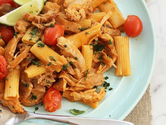 Pasta is combined with shredded chicken.