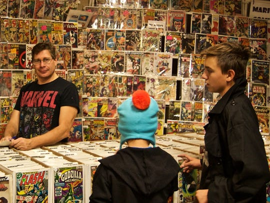 Mario Russo of Mario's Comics poses in front of a wall of comic books Saturday at the SW-Florida  Comic-Con.