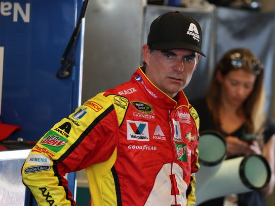 Jeff Gordon waits in his garage as his team works on