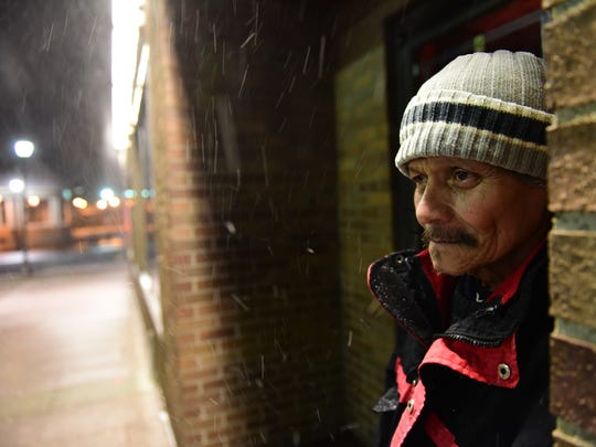 Jose Salinas, of Union City,  waits in a business entryway as snow falls, for the bus to take him home after working the night shift in Rutherford Thursday morning.