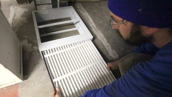 Lukas Havlicek works on installing a new furnace air filter in a San Francisco, California home during a green energy remodel in 2009.