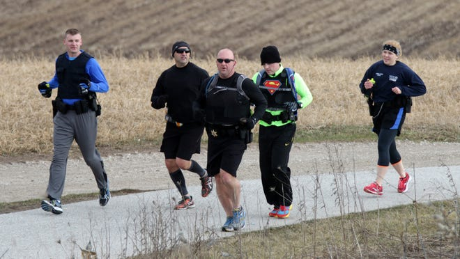 Sheboygan County Sheriff's Dept. Sgt. Matt Spence, center, leads a group of police officers training on the Old Plank Road Trail Friday near Sheboygan Falls. The officers will run in the Cellcom Green Bay Marathon May 17 wearing full police gear.