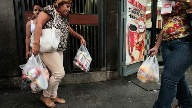 A customer leaves a private supermarket with her purchases in Caracas. Venezuela is running out of the most basic of necessities -- toilet paper.