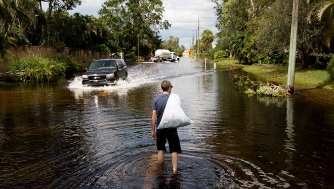 "With a bag of belongings over his shoulder Wednesday, Sept. 13, 2017, Ken Taylor, a resident of Timberwood Village along Island Park Road, wades toward Island Park High School where he parked his car for safe keeping in Island Park, Fla. ""The wind did blow holes in my chimney from the outside. We were open to the elements through the storm,"" Taylor said. ""I would say we got lucky."""