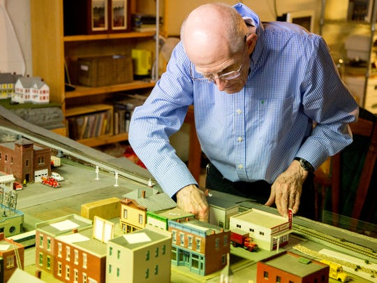 Richard Tabor tinkers with the layout of a miniature model city he's been working on since 2010.