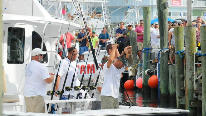 The crew of Two Timing Connie out of Edge Water, Md. celebrate after catching a leading 79lb Wahoo on Tuesday on Day 2 of the 43rd Annual White Marlin Open in Ocean City, Md.