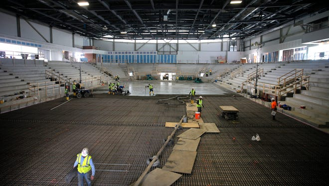 Workers from Ice Builders Inc. pour concrete for the rink floor in the new Gene Polisseni Center on RIT's campus.