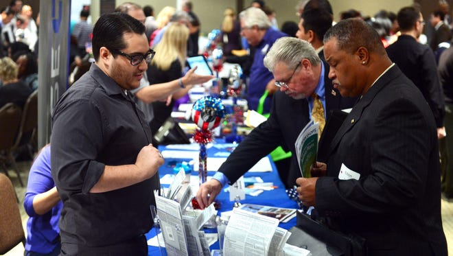 """Prospective job seekers meet Oct. 24 with company reps at the annual """"Honor a Hero -- Hire a Vet"""" job fair in Van Nuys, Calif."""