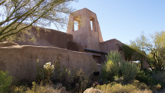 The thick walls and windtower give the Edwards house a look similar to a Southwestern mission church, but the tower, which functions as a passive cooling system, was inspired by traditional Middle Eastern architecture. In the front yard, native plants flourish with minimal intervention for a low-water, low-maintenance landscape.