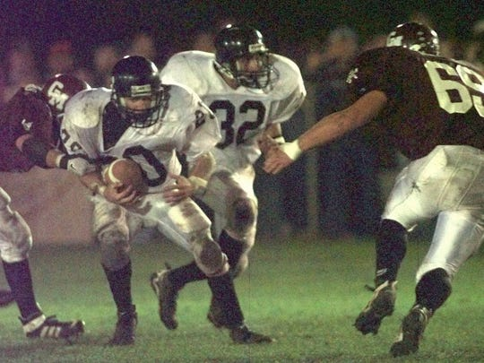LeRoy's Justin Ausher gets past one Red Raider, but Cal-Mum's Jon Steele waits in his path during the 1997 game.