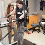 Heidi Santore tries the LiteGait therapy device with assistance from a physical therapist.
