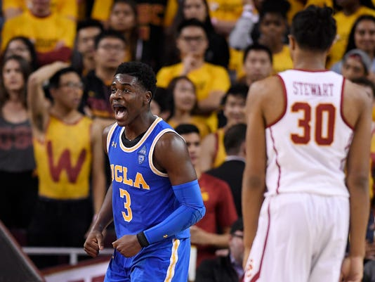 UCLA guard Aaron Holiday, left, celebrates after scoring as Southern California guard Elijah Stewart stands by during the second half of an NCAA college basketball game, Saturday, March 3, 2018, in Los Angeles. UCLA won 83-72. (AP Photo/Mark J. Terrill)
