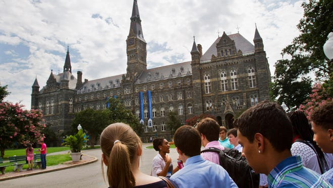 In this July 10, 2013, file photo, prospective students tour Georgetown University's campus in Washington.