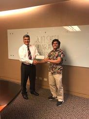 Leonard Calvo, right, presents a $1,000 check to Rodney