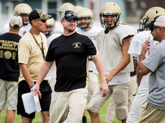 Delone Catholic head coach Corey Zortman grins while talking with quarterback Evan Brady during a team practice on Tuesday, September 12, 2017.