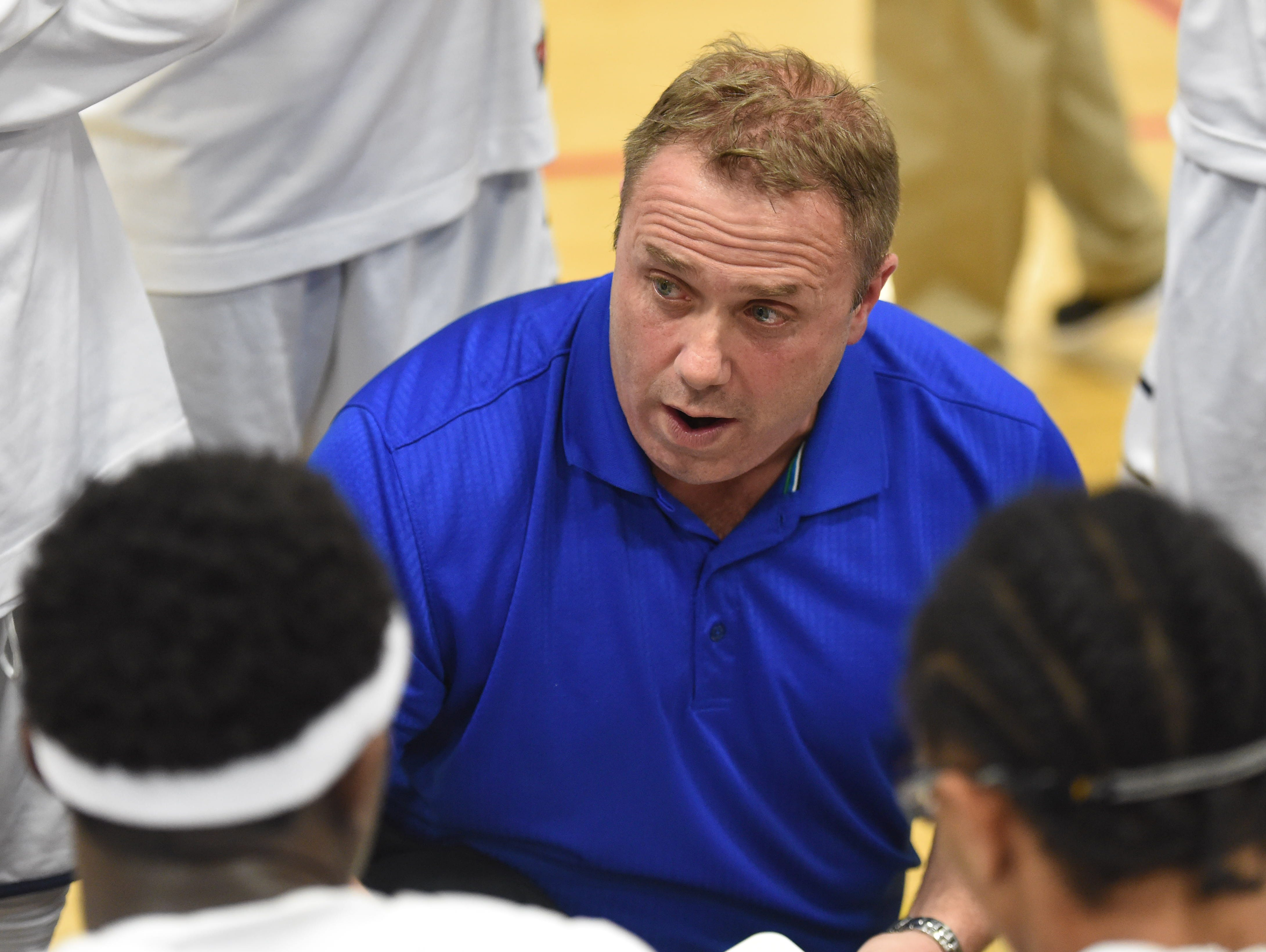 Poughkeepsie High School boys basketball coach Brian Laffin huddles with his team during a game.