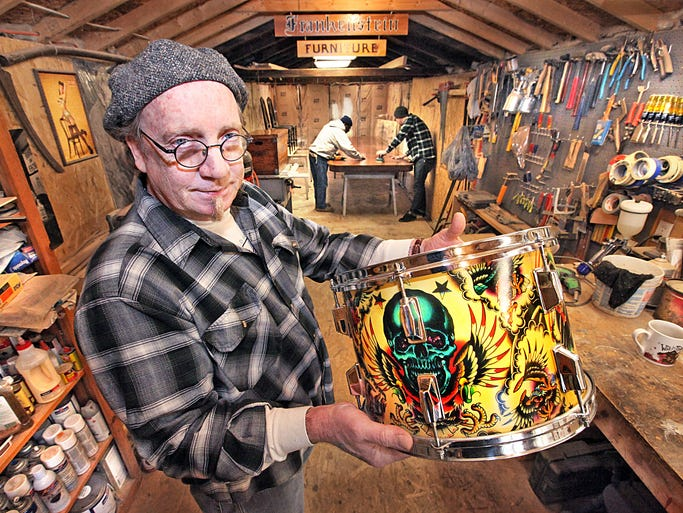 Craig Smith of Frankenstein Furniture displays a custom drum he designed using tattoo patterns. This is the type of work Smith produces in the small business he and his wife, Michelle, started four years ago.
