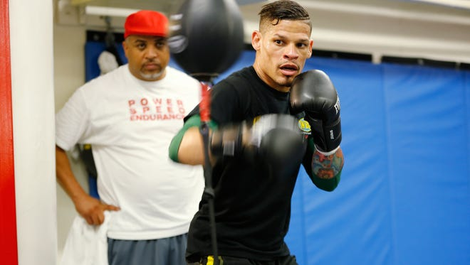 Boxer Orlando Cruz, right, is shown at an open workout at Mendez Boxing Gym, Tuesday, Sept. 24, 2013, New York. Cruz, the number one featherweight contender, is boxing's first openly gay fighter.