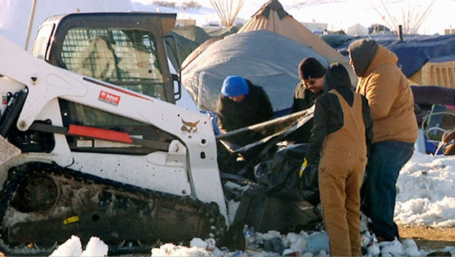 This Monday, Jan. 30, 2017, photo from video provided by KXMB in Bismarck, N.D., shows cleanup beginning at a North Dakota encampment near Cannon Ball where Dakota Access oil pipeline opponents have protested for months. The Standing Rock Sioux has organized the cleanup with the help of the Thunder Valley Community Development Corp. from South Dakota's Pine Ridge Reservation, which has arranged for heavy equipment including front-end loaders, dump trucks and skid-steer loaders. The work could take weeks, and the cost isn't known.