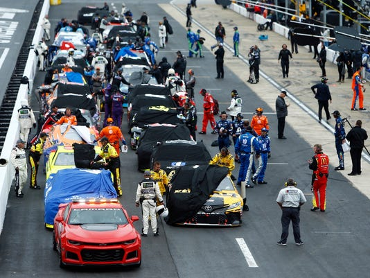 Crews cover their cars as a rain delay is called during a NASCAR Cup Series auto race, Sunday, April 15, 2018, in Bristol, Tenn. (AP Photo/Wade Payne)