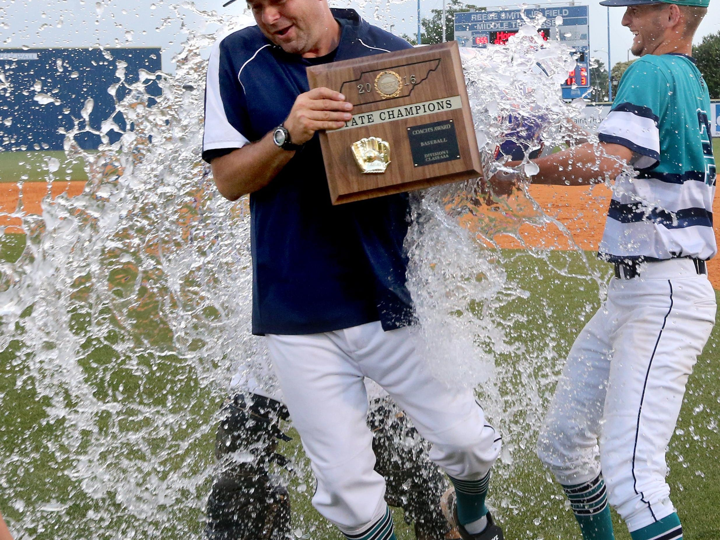 Siegel baseball coach Craig Reavis is doused by players Thomas Marks (12) and Garrett Harvey (22) after Reavis received the coaches award following the Stars' 9-8 win over Arlington in the Class AAA championship.