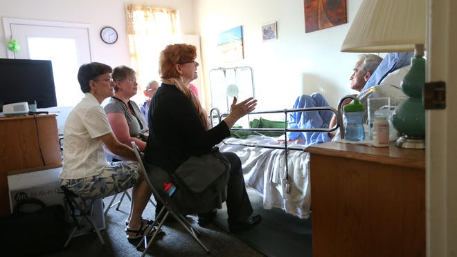 """Deborah Carrithers (center) leads other singers in a visit to a patient at the Abbie Hunt Bryce Home on the Northeastside. """"Our music ... addresses the fears and concerns of those at the end of life,"""" Carrithers said."""