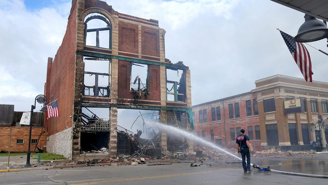 Firefighters sprayed the smoldering remains Sunday of the building at 400 S. Main St. in Sheridan, which had housed a furniture store and classrooms over its 122 years. The blaze at the home of Main Street PowerMAIL started Saturday evening.
