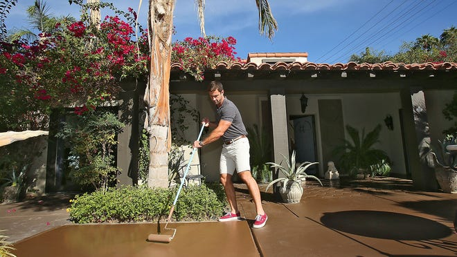 Vacation rental owner Rudi Polak refreshes the paint at the entrance to his property on Camino Carmelita in south Palm Springs on Oct. 23.