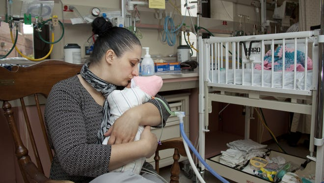 Gracinda Pereira kisses her newborn daughter Amari next to Amari's crib in York Hospital's neonatal intensive care unit. While Amari continues to receive care from doctors and nurses, Pereira juggles visits to the hospital, pumping breastmilk and taking care of her other daughter, age 11, at home.