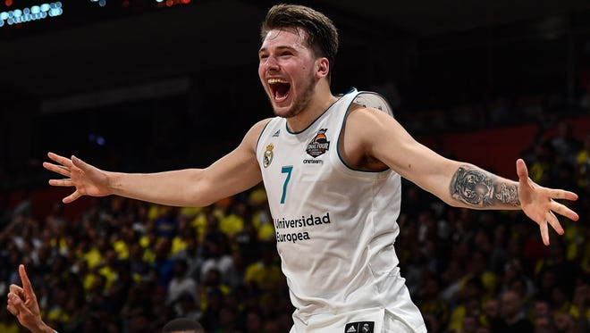 Real Madrid's Slovenian Luka Doncic jumps over the barrier as the team celebrates their 85-80 win over Fenerbahce in the Euroleague Final Four finals basketball match between Real Madrid and Fenerbahce Dogus Istanbul at The Stark Arena in Belgrade on May 20, 2018.
