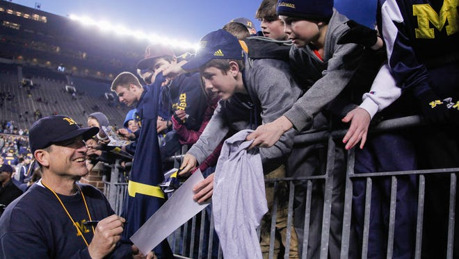 Michigan coach Jim Harbaugh signs autographs after the spring game on Friday, April 1, 2016 at Michigan Stadium.