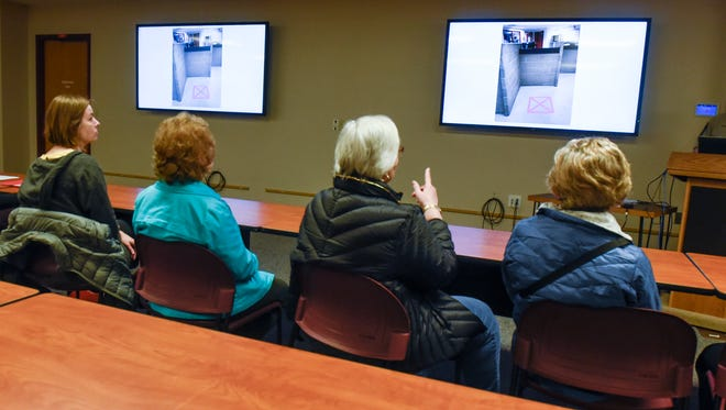Members of Asamblea de Derechos Civilies, also known as Assembly for Civil Rights, view photos of Stearns County Jail intake areas during a presentation Monday, March 19, in St. Cloud.