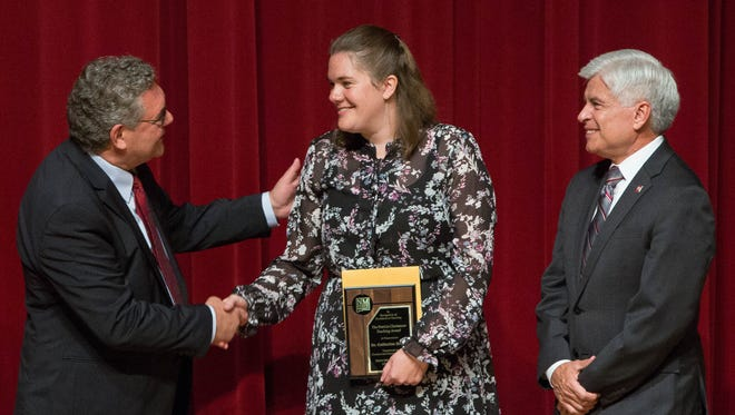 John Floros, left, president of New Mexico State University along with Dan Arvizu, right, chancellor of NMSU congratulate Catherine Brewer, center,  a professor of chemical and material engineering  as she was presented with the Patricia Christmore Faculty Teaching award, Tuesday August 14, 2018 at the 2018 Fall Convocation in Atkinson Recital Hall.