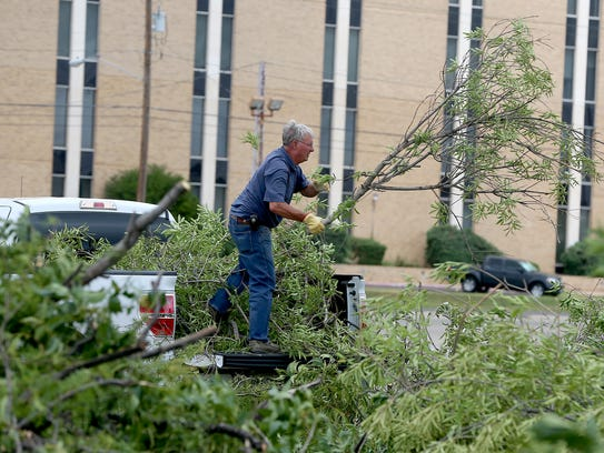 A man unloads tree limbs and other debris at a drop-off