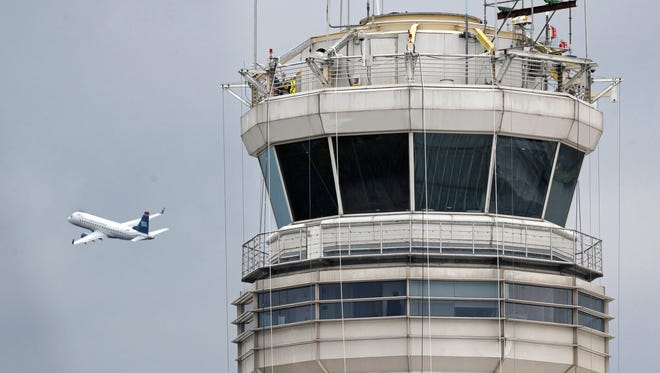 In this March 24, 2011 file photo, a passenger jet flies past the FAA control tower at Washington's Ronald Reagan National Airport.